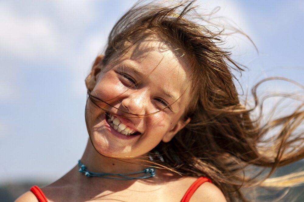 風に吹かれて笑う少女